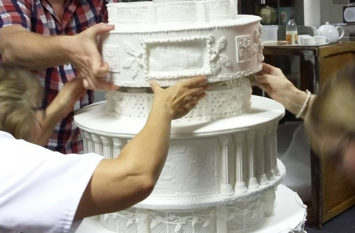 Members of The British Sugarcraft Guild construction team stacking the part completed cakes in the Peek Frean Museum.