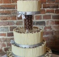 Chocolate - R7 Anne Newiss 3 tier cake with the white chocolate cigarillos, top tier lifted on </br>a centre separator, the centre is filled with Maltesers & the cake topper is Maltesers and hearts on wires