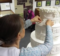 Starting at the top, attaching the piped lace flanges under the top tier.