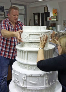 Carefully stacking the cake tiers